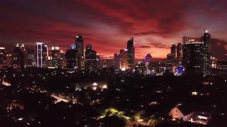 alkony : JAKARTA, Indonesia - October 22, 2019: Beautiful aerial landscape of nightfall in the city with exotic sky and night lights on modern buildings. Shot in 4k resolution from a drone flying upwards Stock mozgókép