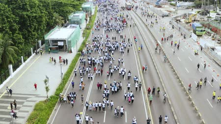 flying upwards : JAKARTA, Indonesia - October 22, 2019: Aerial view of crowded people walking on the Sudirman road during Car Free Day event on the Sunday morning. Shot in 4k resolution from a drone flying upwards