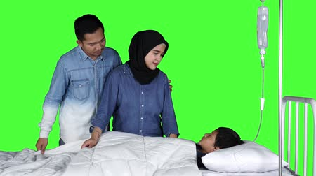 посещающий : Sad young parents visiting their sick son lying on the hospital bed. Shot in 4k resolution with green screen background