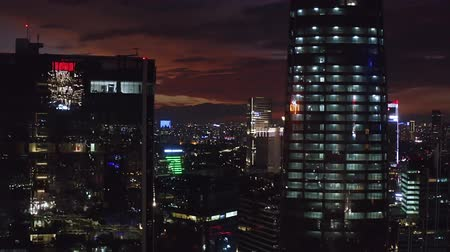 верный : JAKARTA, Indonesia - October 22, 2019: Beautiful aerial view of skyscrapers and night lights in financial district. Shot in 4k resolution from a drone flying from left to right
