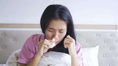 cheirando : Sick woman sniffing nasal spray while sitting on the bed in bedroom at home. Shot in 4k resolution