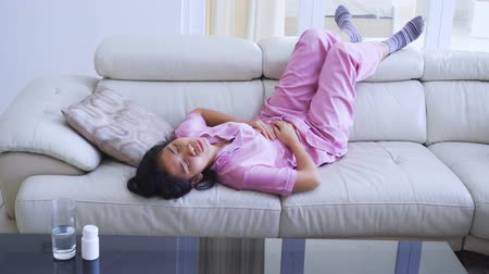 Young woman having stomach ache and lying on the couch while pressing her stomach during menstruation period. Shot in 4k resolution