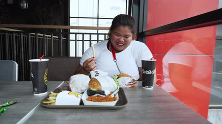 JAKARTA, Indonesia - October 28, 2019: Happy overweight woman eating junk foods and soft drinks on the table in the cafe. Shot in 4k resolution