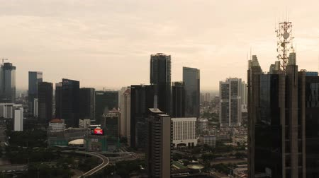 flying upwards : JAKARTA, Indonesia - October 28, 2019: Aerial scenery of silhouette of modern office buildings in central business district at dusk time. Shot in 4k resolution from a drone flying upwards