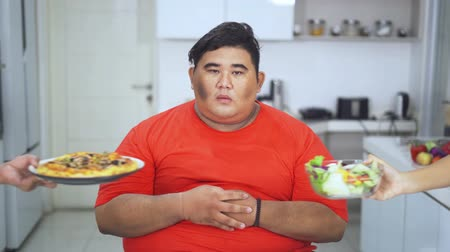 сомнение : Confused overweight young man to choose pizza or vegetables salad in the kitchen at home. Shot in 4k resolution