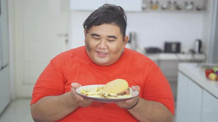 ganancioso : Happy overweight man looking and holding a plate of burger with french fries at home. Shot in 4k resolution
