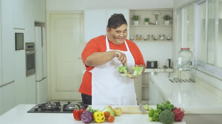 brokkoli : Happy overweight man holding a bowl of vegetables salad while dancing in the kitchen at home. Shot in 4k resolution