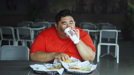 ganancioso : JAKARTA, Indonesia - October 28, 2019: Greedy obese man eating fast foods and soft drink on the table in the cafe. Shot in 4k resolution