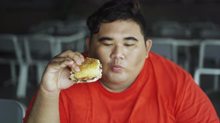 ganancioso : Obese man enjoying burger while sitting in the restaurant. Shot in 4k resolution Vídeos