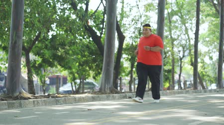 headband : JAKARTA, Indonesia - October 28, 2019: Obese man running at park and taking a rest by sitting on the road under green trees. Shot in 4k resolution