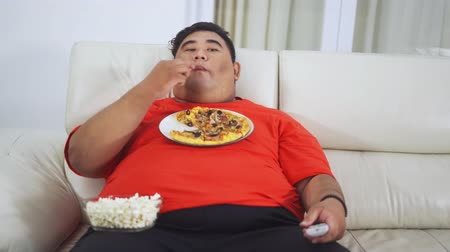 tv channel : Obese young man watching TV while sitting on the sofa and eating popcorn with pizza on his chest in the living room at home. Shot in 4k resolution
