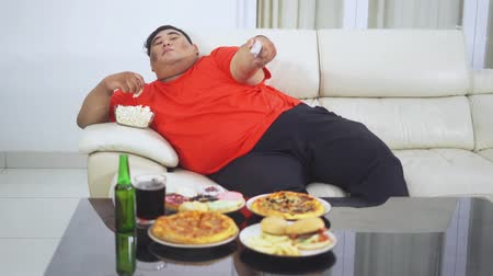 Overweight man relaxing on the sofa while watching TV and eating popcorn with various junk foods on the table at home. Shot in 4k resolution