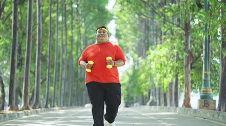 диета : Overweight young man running at the park while carrying two dumbbells and wearing sportswear. Shot in 4k resolution Стоковые видеозаписи
