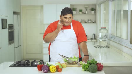 pepinos : Overweight man thinking idea while looking at fresh vegetables on the table in the kitchen at home. Shot in 4k resolution