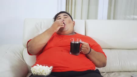 жадный : Overweight man watching TV while eating popcorn and holding a glass of soft drink on the sofa in the living room at home. Shot in 4k resolution Стоковые видеозаписи