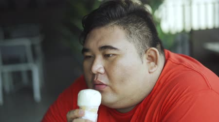 Overweight young man eating a delicious ice cream with waffle cone while sitting in the restaurant. Shot in 4k resolution