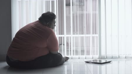 упитанность : Silhouette of stressed overweight man staring at a weight scales while sitting on the floor near the window at home. Shot in 4k resolution Стоковые видеозаписи