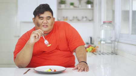 сомнение : Unhappy overweight man trying to eat a little vegetables salad while sitting in the kitchen at home. Shot in 4k resolution Стоковые видеозаписи