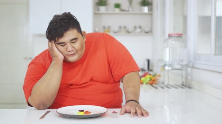 сомнение : Unhappy overweight man looking at a small portion of vegetables salad on the plate while sitting in the kitchen at home. Shot in 4k resolution