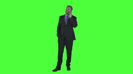 portrait en pied : Successful caucasian businessman talking on mobile phone while standing in the studio and wearing formal suit. Shot in 4k resolution with green screen background