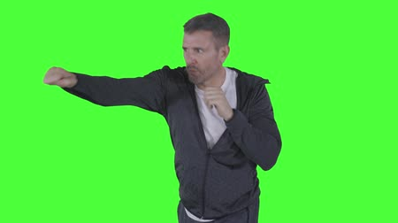 Caucasian man doing boxing exercise while punching something in the studio. Shot in 4k resolution with green screen background