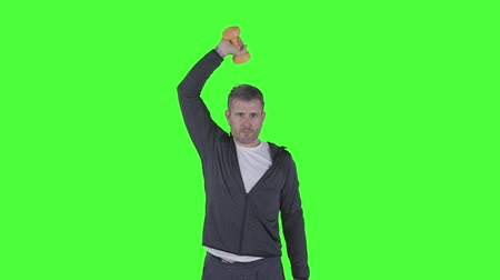 ağır çekimli : Healthy caucasian man doing workout with dumbbells while wearing sweater. Shot in 4k resolution with green screen background Stok Video