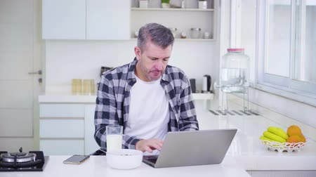 derramado : Caucasian man working with laptop and spill a glass of milk accidentally on the laptop in the kitchen at home. Shot in 4k resolution