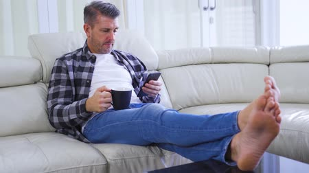 Caucasian man using smartphone while drinking coffee and sitting on the sofa in the living room at home. Shot in 4k resolution