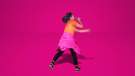 chmiel : Back view of young woman singing in the studio with a microphone. Shot in 4k resolution with pink background