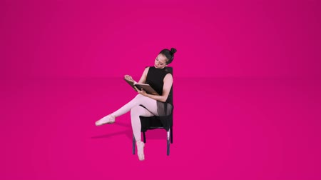 Ballet dancer sitting on the chair while reading a references book in the studio. Shot in 4k resolution with pink background Wideo