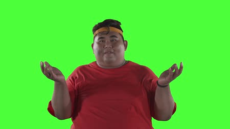 オプション : Funny overweight man shrugging his shoulders in the studio. Shot in 4k resolution with green screen background