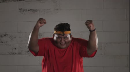headband : Slow motion of happy obese man expressing his success while wearing sportswear with a wall background