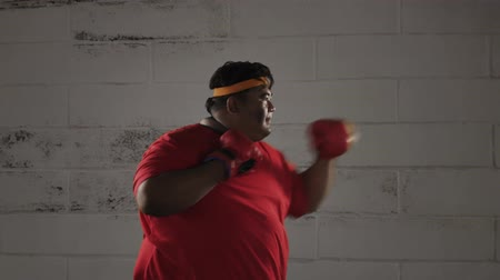 saç bantı : Side view of obese man doing workout by punching something with boxing gloves. Shot in 4k resolution Stok Video
