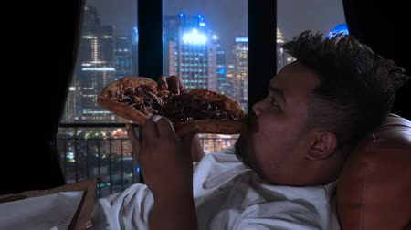 ganancioso : Overweight man eating pizza at night while sitting on sofa in his apartment with city view on the window. Shot in 4k resolution