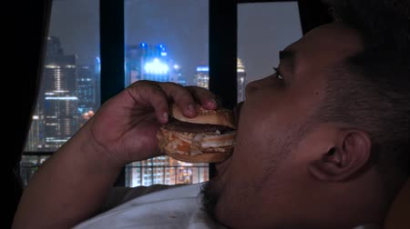 ganancioso : Slow motion of overweight man eating burger at night in his apartment with city view on the window