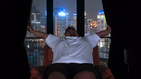 nuda : Overweight man stretching arms and sleeping on the sofa after watching TV at night in his apartment with city view on the window. Shot in 4k resolution
