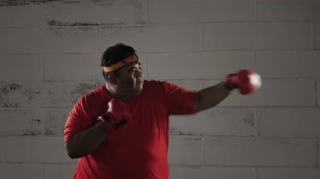 headband : Side view of overweight young man exercising by doing boxing exercise