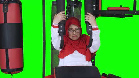 шестидесятые годы : Senior woman doing exercising with gym machine. Shot in 4k resolution with green screen background Стоковые видеозаписи