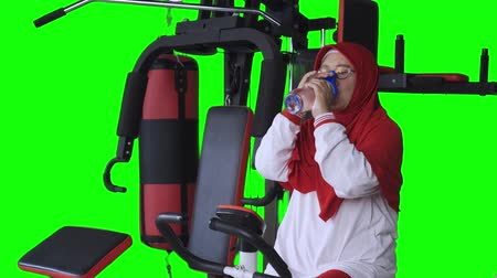 ivászat : Senior woman drinking fresh water while riding exercise bike. Shot in 4k resolution with green screen background Stock mozgókép