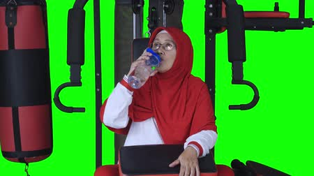 ivászat : Mature woman drinking water while sitting on gym machine. Shot in 4k resolution with green screen background