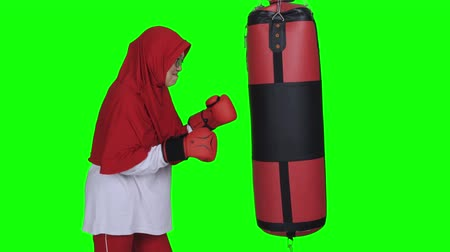 JAKARTA, Indonesia - January 30, 2020: Mature woman doing exercise while punching a boxing sacks. Shot in 4k resolution with green screen background