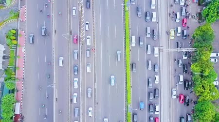 bottleneck : JAKARTA, Indonesia - January 27, 2020: Top down view of cars moving on the tollway and regular road during rush hour with traffic jam. Stock Footage