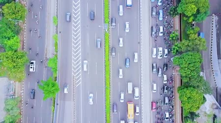 toll : JAKARTA, Indonesia - January 27, 2020: Top down view of vehicle moving on the toll road and regular road during rush hour with traffic jam