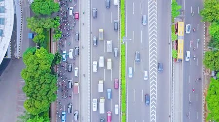 busy line : JAKARTA, Indonesia - January 27, 2020: Top down view of vehicle moving on the regular road and tollway during rush hour with traffic jam Stock Footage