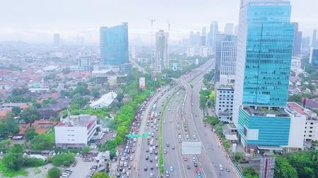 bottleneck : JAKARTA, Indonesia - January 27, 2020: Aerial landscape of tollway during rush hour with cityscape background