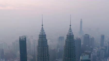 KUALA LUMPUR, MALAYSIA - February 02, 2020: Beautiful aerial view of Petronas Twin Towers peak at misty morning in business district. Shot in 4k resolution from a drone flying down