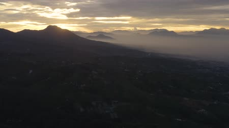 плато : Beautiful aerial footage of village and farmland on the mountain valley at dawn time in the misty morning at Dieng Plateau, Wonosobo, Central Java, Indonesia. Shot in 4k resolution