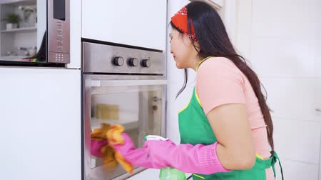 mikrohullámú : Pretty housewife cleaning an oven with a duster and spray in the kitchen at home. Shot in 4k resolution Stock mozgókép