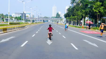 Деятельность выходные : JAKARTA, Indonesia - February 01, 2020: Rear view of happy little girl riding bicycle on the empty road during car free day on the weekend morning. Shot in 4k resolution Стоковые видеозаписи