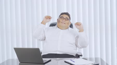 obesity : Obesity businessman dancing to celebrate his success while working in the office room. Shot in 4k resolution